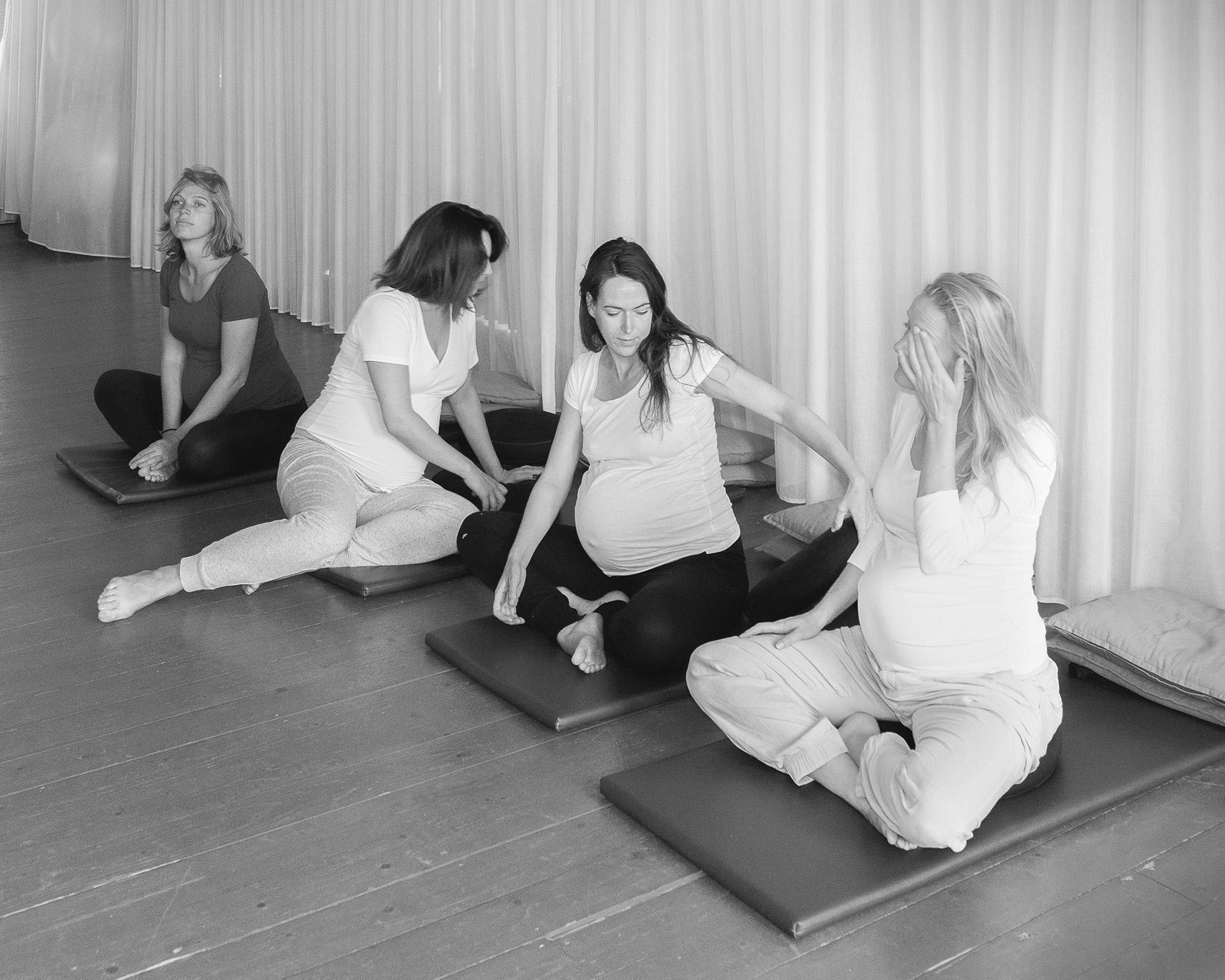 vier zwangere vrouwen op een matje bij de zwangerschapscursus