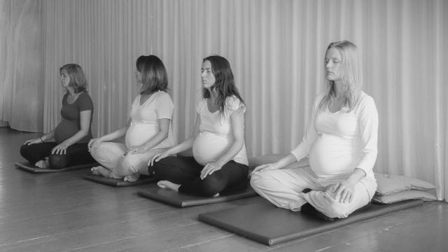 vier zwangere vrouwen zitten met hun ogen dicht bij de zwangerschapscursus